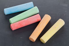 Colorful pieces of chalk on blackboard Stock Images