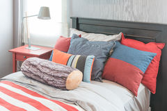 Colorful pillows on bed in single bedroom design. With red table side Royalty Free Stock Image