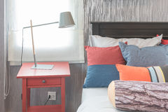 Colorful pillows on bed in single bedroom design. With red table side Royalty Free Stock Photo