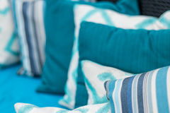 Colorful pillows on a blue sofa. White, blue, dark blue. Stock Photos