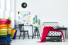 Pillows in bright child`s room. Colorful pillows in bright child`s room with red blanket on the bed and yellow clock on a stool near desk with chair Royalty Free Stock Photos