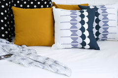 Colorful pillows on a sofa with white brick wall i Royalty Free Stock Photography