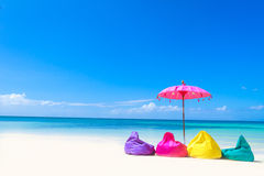 Colorful pillows and umbrella on tropical sea and beach b Stock Photography