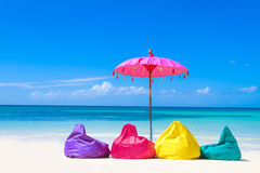 Colorful pillows and umbrella on tropical sea and beach b Royalty Free Stock Image