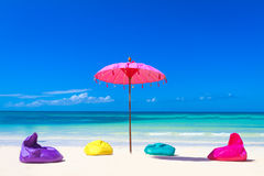 Colorful pillows and umbrella on tropical sea and beach b Stock Image