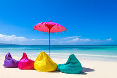 Colorful pillows and umbrella on tropical sea and beach b Stock Photos