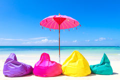 Colorful pillows and umbrella on tropical sea and beach b Royalty Free Stock Photos