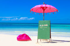 Colorful pillows and umbrella on tropical sea and beach b Stock Images