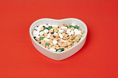 Colorful pills. In heart shape plate on red background Stock Image