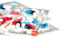 Colorful pills on american dollars, cost of medical health care Royalty Free Stock Image