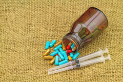 Colorful pills , bottle tablets , syringes and needle lie strewn Stock Photo