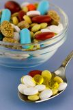 Colorful pills in bowl and spoon Royalty Free Stock Photos