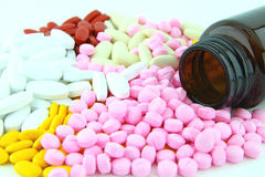 Colorful pills and brown bottle Stock Photos