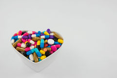 Colorful pills and capsule in a cup on white background Royalty Free Stock Photos