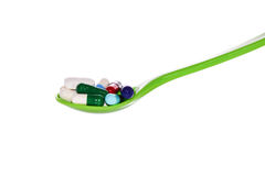 Colorful pills and Capsule on a Green spoon Royalty Free Stock Photography