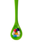 Colorful pills and Capsule on a Green spoon. Stock Photos
