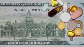 Banknotes and drugs. Colorful pills and capsules on the hundred dollar bill, top view Stock Images