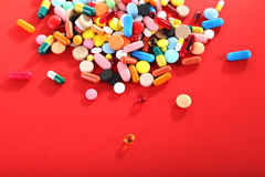Colorful pills. Different colorful pills on red background Royalty Free Stock Photography