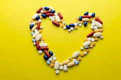 Colorful pills drugs and tablets. Colorful pills and tablets in shape of heart Royalty Free Stock Image