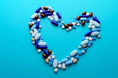 Colorful pills drugs and tablets. Colorful pills and tablets in shape of heart Stock Image