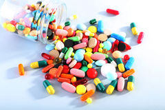 Colorful pills. In glass jar on grey background Royalty Free Stock Photo