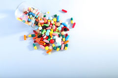 Colorful pills. In glass jar on grey background Stock Photo
