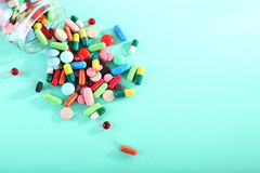 Colorful pills. In glass jar on mint background Stock Photo