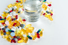Colorful pills and glass of water, on white background. Colorful pills and glass of water, on white background stock photo