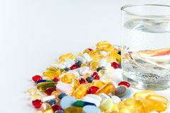Colorful pills and glass of water, on white background. Colorful pills and glass of water, on white background royalty free stock images