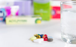 Colorful pills and glass of water, on white background. Royalty Free Stock Photos