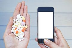 Colorful pills and medicines with smartphone in the woman hands. royalty free stock images