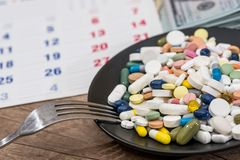 Pills on plate on a calendar medication. Colorful pills on plate on a calendar medication Royalty Free Stock Image