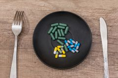 Colorful pills in plate with spoon. On wooden background Royalty Free Stock Photography