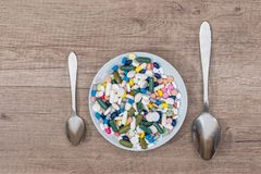 Colorful pills in plate with spoon. On wooden background Stock Photos