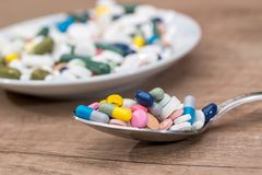 Colorful pills in plate with spoon on wooden Stock Images