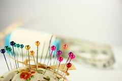 Colorful pin on pin cusion Stock Images