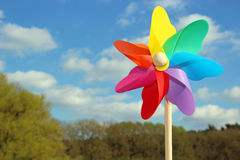 Colorful pin wheel in front of sky and trees royalty free stock images