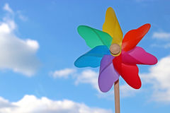Colorful pin wheel, sky with white clouds stock photos