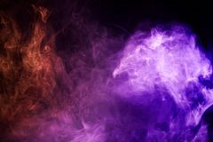Background from the smoke of vape. Colorful pink and blue smoke  on a black isolated background. Background from the smoke of vape Stock Image