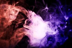 Background from the smoke of vape. Colorful pink  and blue a smoke  on a black isolated background. Background from the smoke of vape Stock Image
