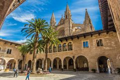 Royal Palace in Palma Mallorca with Tourists. Tourists touring the the Royal Palace in Palma Mallorca with the Cathedral seen in the background Royalty Free Stock Photo