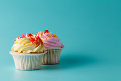 Colorful pink cupcake on aquamarine background Stock Images