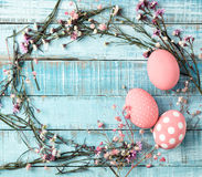 Colorful pink eggs and flower frame on blue wood Royalty Free Stock Photography