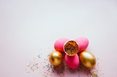 Colorful pink and golden easter eggs with confectionery sprinkling Royalty Free Stock Photos