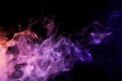 Background from the smoke of vape. Colorful pink a smoke  on a black isolated background. Background from the smoke of vape Stock Photo