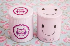 Colorful Pink Tin Storage Containers on Floral Pattern Stock Image