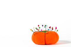 Pin cushion. Colorful pins on pin cushion against white background. Plenty of copyspace royalty free stock images
