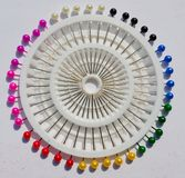 Colorful pins in a pin holder. Colorful pins arranged in a circular pattern in a pin holder royalty free stock photography