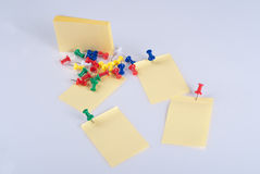 Colorful pins and yellow note Royalty Free Stock Photo