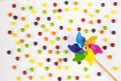 Colorful pinwheel and candies on white background. Top view. Flat lay stock photography